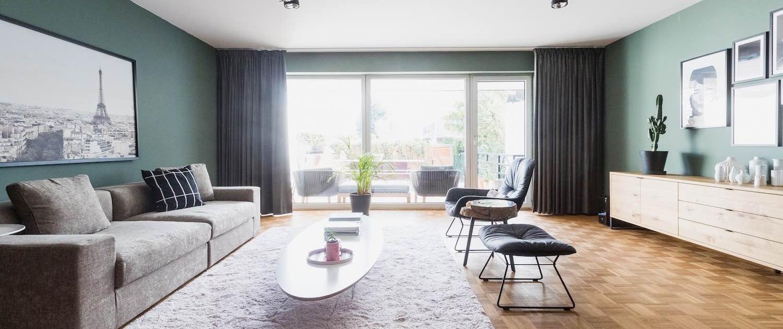 Der Parkettboden im Wohnzimmer harmoniert perfekt mit dem Sideboard aus Holz und der grünen Wandfarbe. Graue Akzente im Raum verleihen einen edlen Look. Das Konzept für die Inneneinrichtung stammt von Malchow Interior Design.