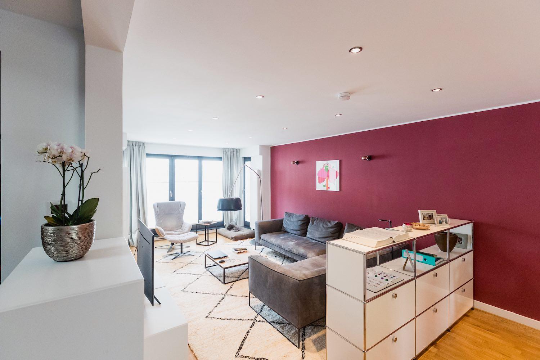 Im Frankfurter Wohnzimmer harmonieren verschiedene Designermöbel in hellen und dunklen Farben miteinander. Weiß- und Grautöne passen gut zur farbigen Wand.