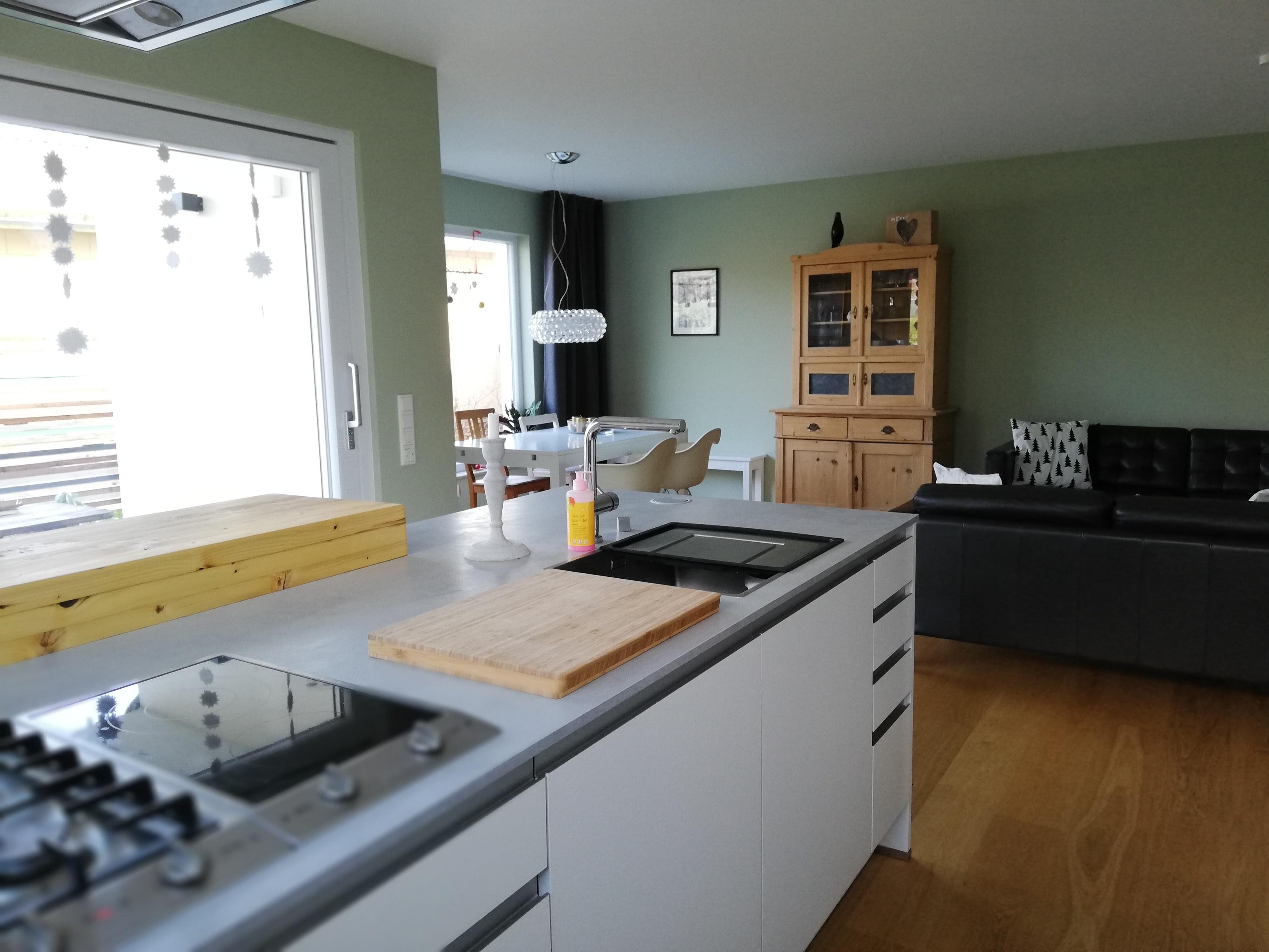 Nach der Einrichtungsberatung kommen die Möbel vor grünen Wand erst richtig zur Geltung.